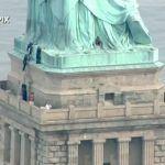 Mujer escala la Estatua de la Libertad durante marcha Anti-Trump